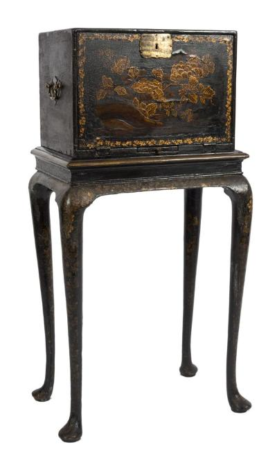 An 18th Century Anglo-Indian and chinoiserie decorated cabinet on stand, with peony and chrysanthemum blossom and foliage heightened in gilt on a black lacquer ground, the cabinet with a hinged fall enclosing an ivory inlaid interior with stellar, foliate and lozenge geometric designs, containing an arrangement of six drawers, having a candle slide below and brass drop carrying handles to the sides, the stand on cabriole legs, terminating in pad feet, the cabinet 44.5cm (1ft 5 1/2in) wide, the stand 53cm (1ft 9in) wide, overall height 103.5cm (3ft 4 3/4in), with restorations.