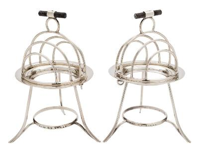 Sale FS36; Lot: 0001: Asprey & Co, a pair of silver plated toast racks of domed form with four divisions, raised on swept legs, burners lacking, stamped A&Co, Asprey, London, 20446, 19cm high.