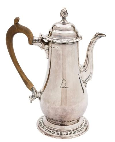 A George III old Sheffield plated coffee pot, struck three times for Henry Tudor & Co, circa 1760-65 crested, of baluster form, the domed hinged lid with pineapple finial, reeded spout, raised on a circular foot, 25.5cm high.