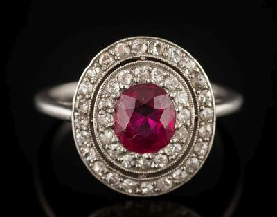 Sale FS36; Lot: 0272: An early 20th century platinum, ruby and diamond oval cluster ring with central oval ruby approximately 6.7mm long x 5.5mm wide x 3.4mm deep, estimated to weigh 0.9ct, millegrain-set within a double surround of circular diamonds, ring size L.
