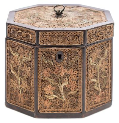 A George III mahogany and quillwork tea caddy of octagonal outline, the hinged lid and sides decorated with quilling decoration of floral sprays and neo-classical urn decoration, with lidded interior, 13cm wide.