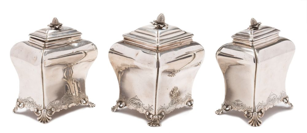 Sale FS37; Lot: 0346: A set of three George II tea caddies, maker Pierre Gillois, London 1754/55/56 of bombe outline, each with shallow domed lift-off lid and strawberry finial, the waisted bodies with chased scroll decoration raised on curved shell feet,(the larger caddy missing one foot), contained in a Victorian rosewood fitted box, 29cm wide, total weight of silver 23.38ozs.