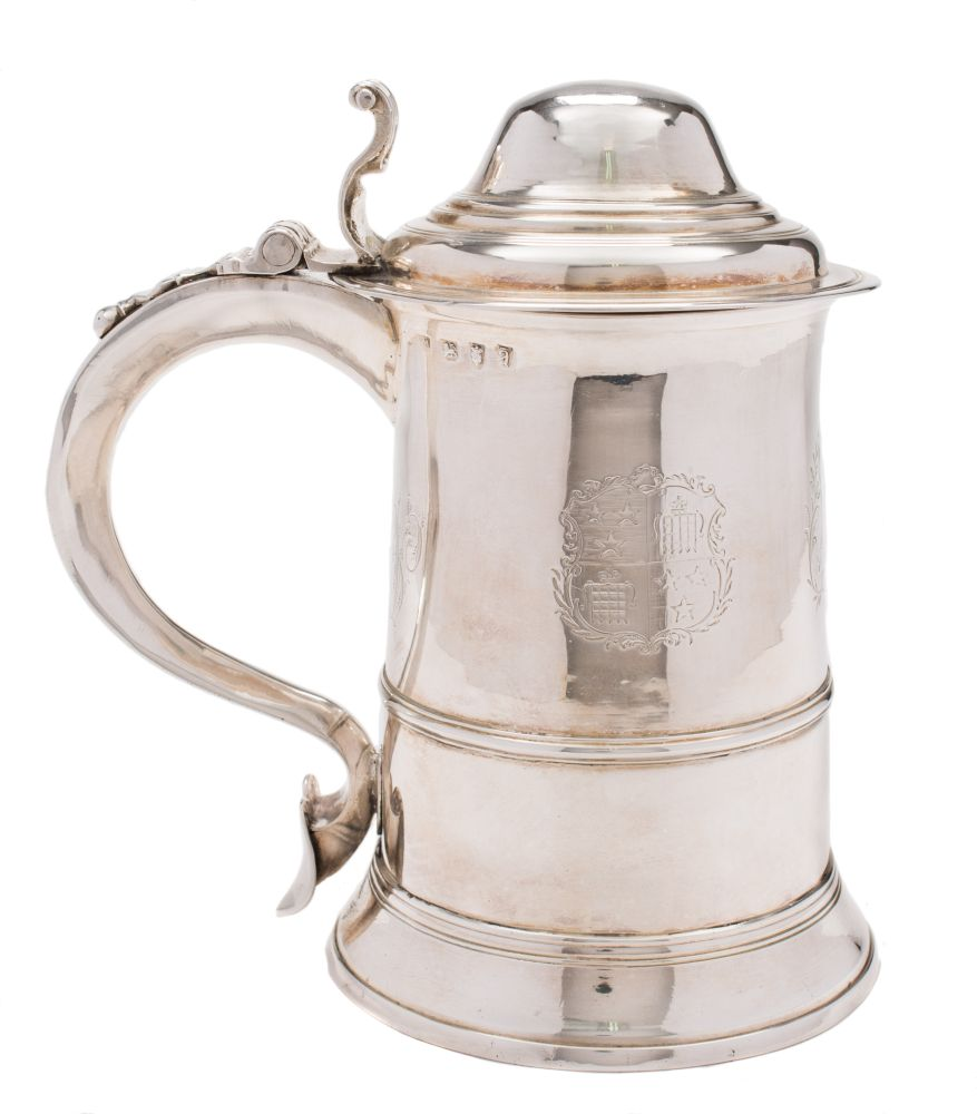 Sale FS37; Lot: 0365: A George III silver tankard, maker William Turton, London, 1776 crested and initialed, with stepped domed hinged lid with scroll thumbpiece, of cylindrical form with reeded girdle and scroll handle on a spreading circular foot, 20cm high, 26.25cm.
