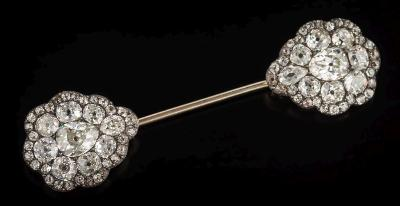 Sale FS37; Lot: 0485: A diamond mounted jabot pin with two pear-shaped clusters, each pave-set with a central pear-shaped diamond approximately 1.0cts within a surround of round old brilliant-cut diamonds, the diamonds estimated to weigh a total of 7 0cts, 68mm long overall.