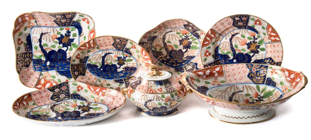 Sale FS37; Lot: 0788: A Coalport porcelain 'Japan' pattern part dessert service painted and gilded with rockwork, trees, flowering shrubs and lattice panels in underglaze blue with iron-red and green enamels, circa 1805-10, comprising eighteen plates, four lobed square dishes, four scallop shaped dishes, four shaped oval dishes, an oval pedestal dish, a sauce tureen, two covers and two stands, thirty six pieces [one stand damaged, minor wear to gilt]. * Cf. Geoffrey A Godden 'Coalport and Coalbrookedale Porcelains' plate 26 for a similar dessert service in the Royal Collection.