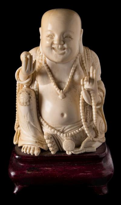 Sale FS37; Lot: 0880: A late 19th century Chinese carved ivory figure of a seated Buddah wearing loose robes and adorned with beads, mounted on a polished wood stand, total height 14cm.