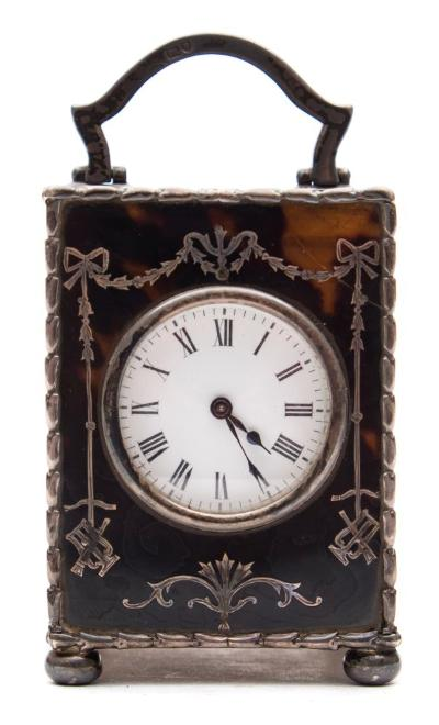 Sale FS37; Lot: 1030: An Edwardian miniature tortoiseshell and silver carriage clock the eight-day duration timepiece movement having a platform lever escapement, the round dial with black Roman hour numerals and blued steel spade hands, the tortoiseshell case inset with silver decoration, mounts and carrying handle, hallmarked for London 1906, height 9cm (handle up) 7.5cm (handle down).