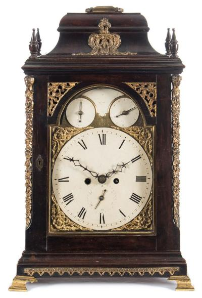Sale FS37; Lot: 1056: Starey, London, an ebonised bell-top bracket clock the eight-day duration, double-fusee movement having a verge escapement and striking the hours on a bell with pull hour repeat, the backplate engraved with floral and rococo decoration and signed Starey, London within a cartouche, the eight-inch brass break-arch dial having a painted centre with black Roman hour numerals and decorative blued steel hands, with two painted subsidiary dials within the arch for 'strike/silent' and alarm setting either side of a shaped inset panel signed for the maker Starey, London, with engraved decoration below and with cast-brass floral spandrels to the four corners, the case ebonised on fruitwood, with applied cast-brass mounts to the lower front moulding, the canted corners, the bell-top and inset either side of the top of the dial, with turned wooden finials and surmounted by a brass carrying handle, with decorative cast side frets, standing on brass bracket feet, height 58cm, handle up, 54cm handle down. * Biography John Starey is recorded as working at the Royal Exchange, London from circa 1770, becoming a Freeman of the Clockmakers Company in 1785 until his death in 1800.