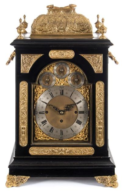 Sale FS37; Lot: 1057: A large Victorian chiming bracket clock the eight-day duration, triple-fusee movement with anchor escapement, striking the hours on a gong and the quarters on a set of nine-bells, with engraved decoration to the backplate, the break-arch brass dial having a raised silvered chapter ring with black Roman numerals and decorative blued steel hands, three further silvered subsidiary dials within the arch for 'Chime'Silent', 'Regulation' and 'Westminster Chime/Chiming on Eight Bells', with a matted centre and cast-brass c-scroll spandrels to the four corners and arch, the ebonised case having a cast-brass gilded locking top opening to reveal the movement, surmounted by a brass carrying handle, with applied raised classical decorative friezes to either side, below and above the dial, with matching panels to each case side below a cast-brass handle, standing on matching bracket feet, signed under the chapter ring JC Jennens, London, height 66cm handle up, 62cm handle down. * Biography Possibly John Creed Jennens (& Son) working in London circa 1863 until at least 1875.