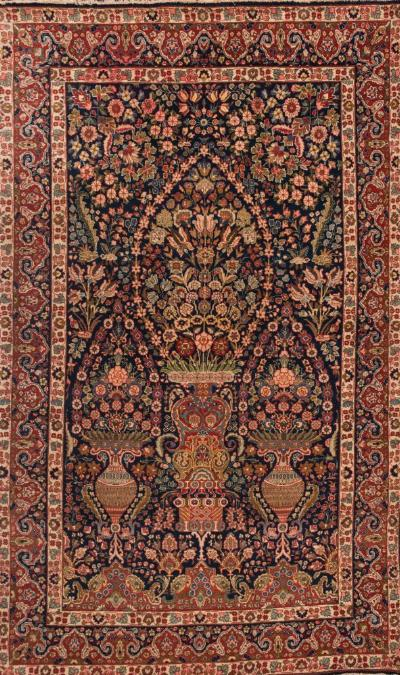 Sale FS37; Lot: 1083: A Tabriz rug, of large size, the indigo field with three urns of flowering foliage and all over floral foliate designs, enclosed by a red and indigo shaped and pointed border, 311cm x 193cm.