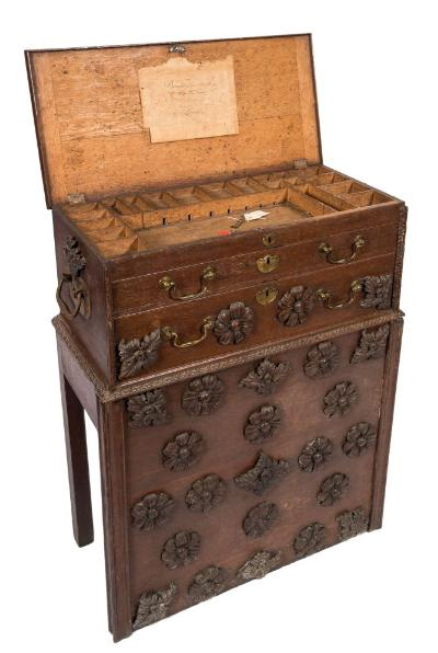 Sale FS37; Lot: 1111: A carpenter's 18th Century oak tool chest on a stand, the chest with a hinged top enclosing a fitted interior with various divisions, containing two long drawers below, the lower drawer and stand with bold applied carved flowerheads and paterae, the sides with applied iron handles and carved paterae above, 79cm (2ft 7in) wide.