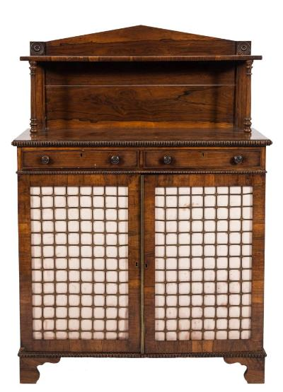 Sale FS37; Lot: 1169: A late Regency rosewood chiffonier, of small size, with reel turned mouldings, the shelved superstructure with angled arch ledge back, roundel ornament and ring turned column uprights, containing two frieze drawers, the cupboard below enclosed by a pair of brass lattice and silk panel doors, on bracket feet, 92.5cm (3ft 0 1/2in) wide.