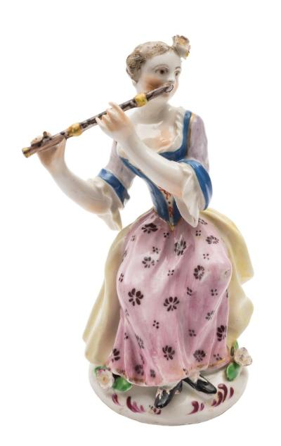 A Bow figure of a seated lady flautist wearing a yellow cloak, blue and pale purple bodice with pink floral skirt, circa 1756-58, 13cm high [one finger lacking, restoration to one foot].