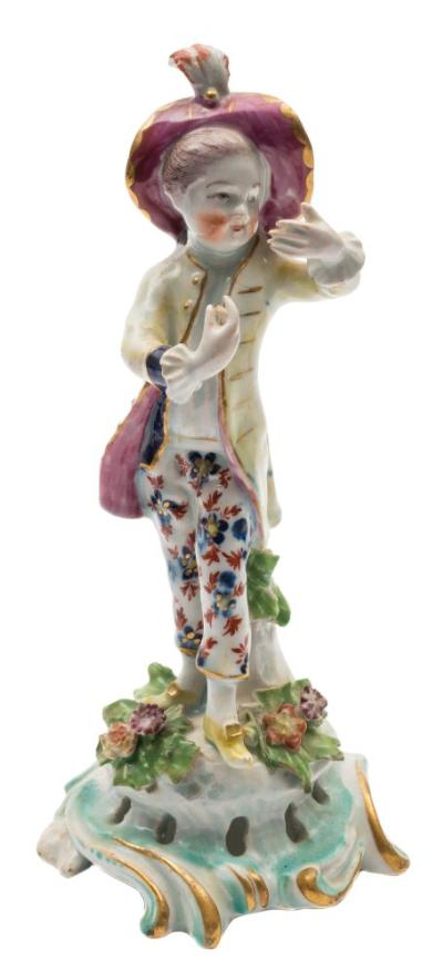A Bow figure of a 'New Dancer' wearing a pink wide brimmed hat with feather plume, pale yellow frock coat and floral decorated pantaloons, on pierced scrollwork base, iron-red anchor and dagger mark, circa 1765-70, 19.5cm high [minor chip to coat and applied leaves].