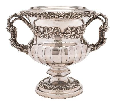Sale FS37; Lot: 0158: A 19th century silver plated twin handled wine cooler crested, with fluted body having bands of acorns and oak leaf decoration, on a knopped stem and raised circular spreading foot, with liner, 25cm high.