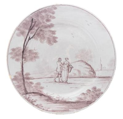 Sale FS37; Lot: 0720: A Bristol delftware plate painted in manganese with a lady and gentleman standing in an extensive landscape with sponged trees, a church in the background, circa 1740-50, 26.5cm diameter [minor chip and glaze losses].