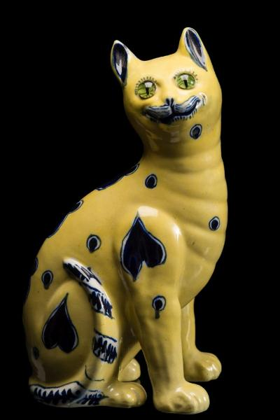 A Mosanic pottery cat modelled seated and painted with blue circle and heart motifs on a yellow ground, with inset glass eyes, early 20th century, 34cm high.