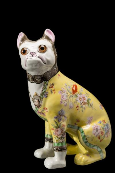 A Galle-style pottery pug modelled seated and transfer decorated with flowers on a yellow ground, the grotesque visage with inset glass eyes, early 20th century, 30cm high.