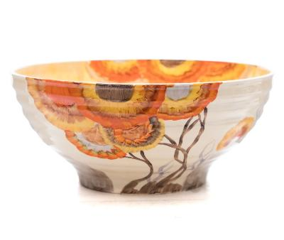 A Clarice Cliff Bizarre bowl in the Rodanthe pattern of ribbed circular form (shape 633) the interior and exterior painted with bright orange and yellow blooms, Bizarre backstamp, circa 1934-36, 24cm diameter.