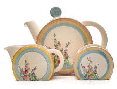Sale FS37; Lot: 0764: A Clarice Cliff three-piece tea service in the Hollyhocks pattern of Bonjour shape each painted with blooms within brown, yellow and turquoise bands, Wilkinson backstamps circa 1936-37, teapot 14cm high.16.