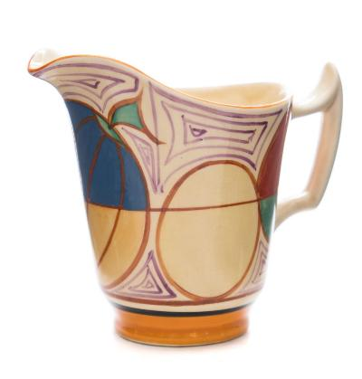 A Clarice Cliff Fantasque milk jug of helmet shaped form decorated in the Melon (Picasso Fruit) pattern in red, green, yellow and blue, Fantasque and Bizarre backstamps, circa 1930-31, 10.5cm high, [blue over painted].
