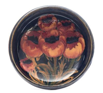 A Moorcroft Tudric pewter mounted bowl tubelined in the Poppies pattern in red, orange and green on a blue ground, set on a planished pewter foot, stamped Moorcroft, Tudric, Made in England, 01312, circa 1925, 25cm diameter.