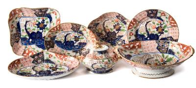 A Coalport porcelain 'Japan' pattern part dessert service painted and gilded with rockwork, trees, flowering shrubs and lattice panels in underglaze blue with iron-red and green enamels, circa 1805-10, comprising eighteen plates, four lobed square dishes, four scallop shaped dishes, four shaped oval dishes, an oval pedestal dish, a sauce tureen, two covers and two stands, thirty six pieces [one stand damaged, minor wear to gilt]. * Cf. Geoffrey A Godden 'Coalport and Coalbrookedale Porcelains' plate 26 for a similar dessert service in the Royal Collection.