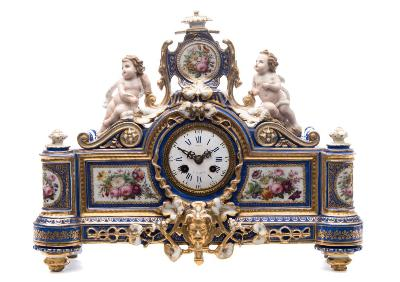 Sale FS37; Lot: 0837: A Paris porcelain figural mantel clock the cartouche shaped case with central mask flanked by pillars and surmounted by a pair of semi - naked putti flanking a flattened urn, the blue ground with gold and tooled gold decoration with four panels enamelled with garden flowers, the enamel dial with Roman and Arabic numerals, the dial and movement signed Rey â Paris, mid 19th century, 40cm wide.