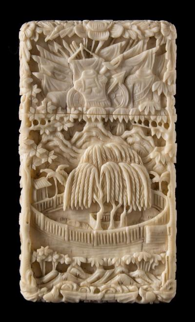 A 19th century Cantonese carved ivory card case the lift off lid carved with European military trophies, the base decorated with a village and garden landscape, 8.5cm high.