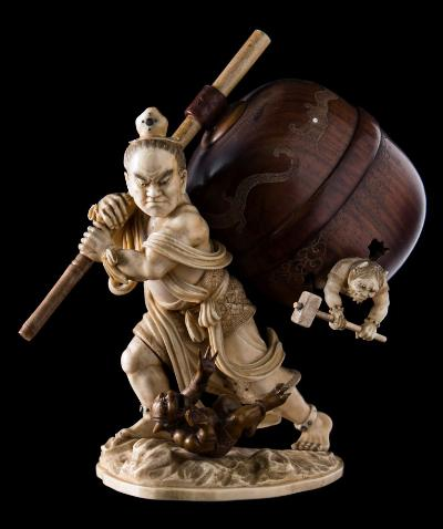 A fine Japanese ivory and boxwood okimono of Nio slaying oni demons carrying a carved hardwood temple bell over his shoulder whilst demons tumble from the bell, signed to a red lacquered tablet Kyokusui, Meiji period, 20cm high.