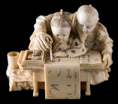 Sale FS37; Lot: 0914: A Japanese carved ivory okimono of a teacher and pupil at a table learning to write the alphabet, signed to the base Ryokoku, Meiji period, 9cm wide.
