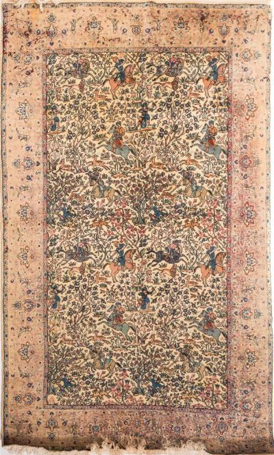 A Qum rug, the ivory field with an all over design of equestrian hunting figures and animals amidst flowering trees and plants, enclosed by a main beige palmette and flowerhead meander border, 220cm x 137cm.