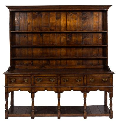 An 18th Century oak dresser with a later shelved superstructure, having a moulded cornice, the base containing four short drawers in the shaped and ogee pointed apron on turned baluster legs, united by a pot board base with block feet, 216cm (7ft 1in) wide, 220cm (7ft 2 1/2in) high.