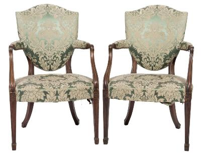 Sale FS37; Lot: 1142: A set of four early 19th Century mahogany open armchairs, in the Hepplewhite taste, with upholstered stuff over shield-shaped backs, padded and moulded arm supports and bowed upholstered stuff over seats, on moulded square tapered legs, headed with carved paterae, terminating in spade feet.
