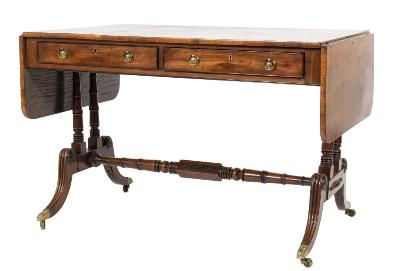 Sale FS37; Lot: 1162: A Regency mahogany sofa table, the hinged top with a rosewood crossbanded border and rounded corners, fitted with two short frieze drawers with ebonised cockbeading on ring turned column end and dual splayed reeded legs, united by a similar stretcher and terminating in brass foliate cappings and castors, the top 66cm (2ft 2in) x 162.5cm (5ft 4in) extended.