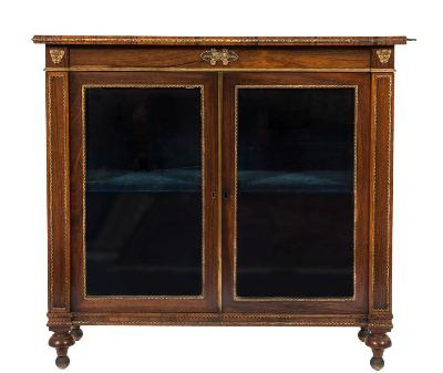 Sale FS37; Lot: 1164: A Regency rosewood and gilt metal mounted dwarf display cabinet with a satinwood crossbanded top, the beaded frieze with central mask, paterae and anthemion ornament, enclosed by a pair of glazed panel doors flanked by pilaster stiles, headed with masks, raised on short turned tapered feet, 92.5cm (3ft 0 1/2in) wide, 85.5cm (2ft 9 3/4in) high.