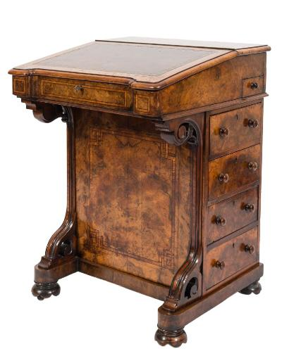 A Victorian walnut, tulipwood crossbanded and inlaid Davenport, bordered with ebonised lines, the superstructure with a sloping hinged fall with tooled leather inset panel enclosing a maple lined interior with two small drawers, the side containing a hinged fitted pen drawer and four short drawers below, the front with moulded scroll uprights, on bun feet with castors, 54cm (1ft 9 1/4in) wide.
