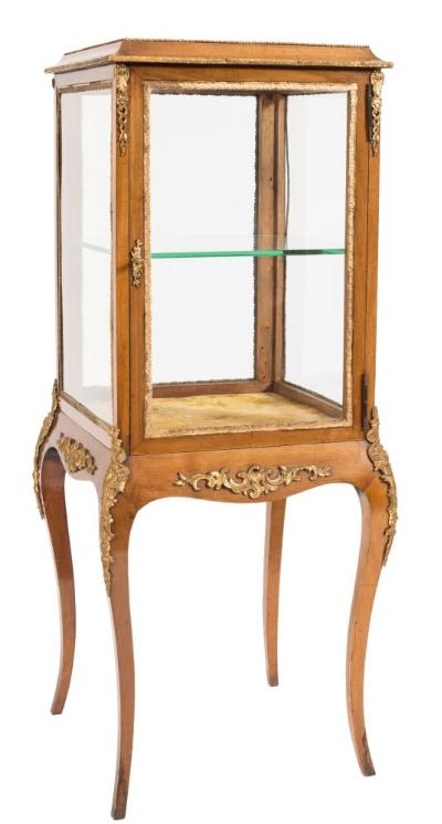 A French mahogany and gilt metal mounted square bijouterie display cabinet, with a bevelled glass panel top, glazed panel sides and enclosing door with plate glass shelf, having a shaped apron with applied foliate scrolls on cabriole legs with cabochon foliate ornament, 42cm (1ft 4 1/2in) square, 110cm (3ft 7 1/4in) high.