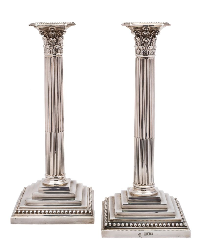 Sale FS38; Lot: 0015: A pair of Victorian silver Corinthian column candlesticks, maker William Hutton & Sons Ltd, London, 1900 with beaded sconces, foliate capitals on stop fluted columns and stepped weighted bases, 29cm high.
