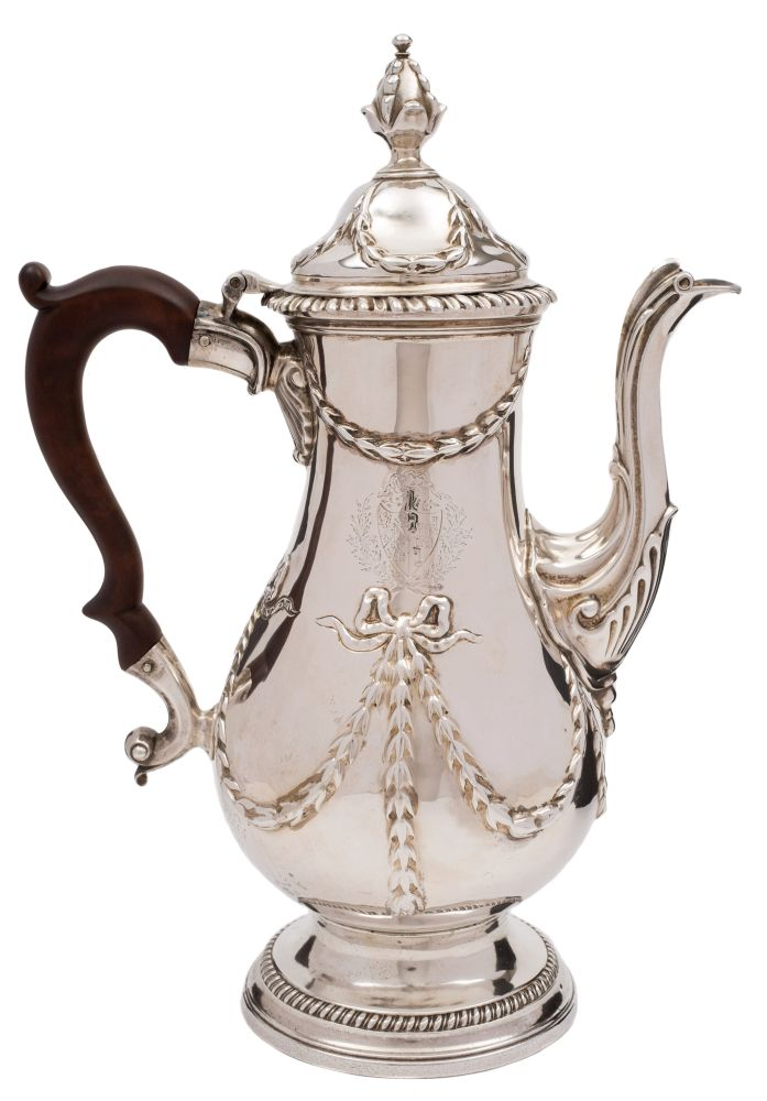 Sale FS38; Lot: 0152: A George III silver coffee pot, maker James Young, London, 1772 crested, with domed hinged lid, tied garland decoration to the body, acanthus decorated spout, on a circular gadrooned and spreading foot, 28cm high. 827.1gms, 29.15ozs.