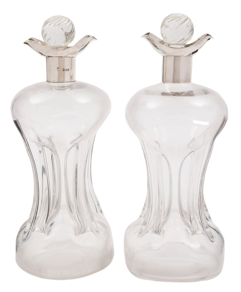 Sale FS38; Lot: 0160: A pair of late Victorian silver mounted clear glass decanters, maker William Gibson & John Landman, London, 1895 of hour glass form with oval-shaped spouts and writhen stoppers, 29cm high.