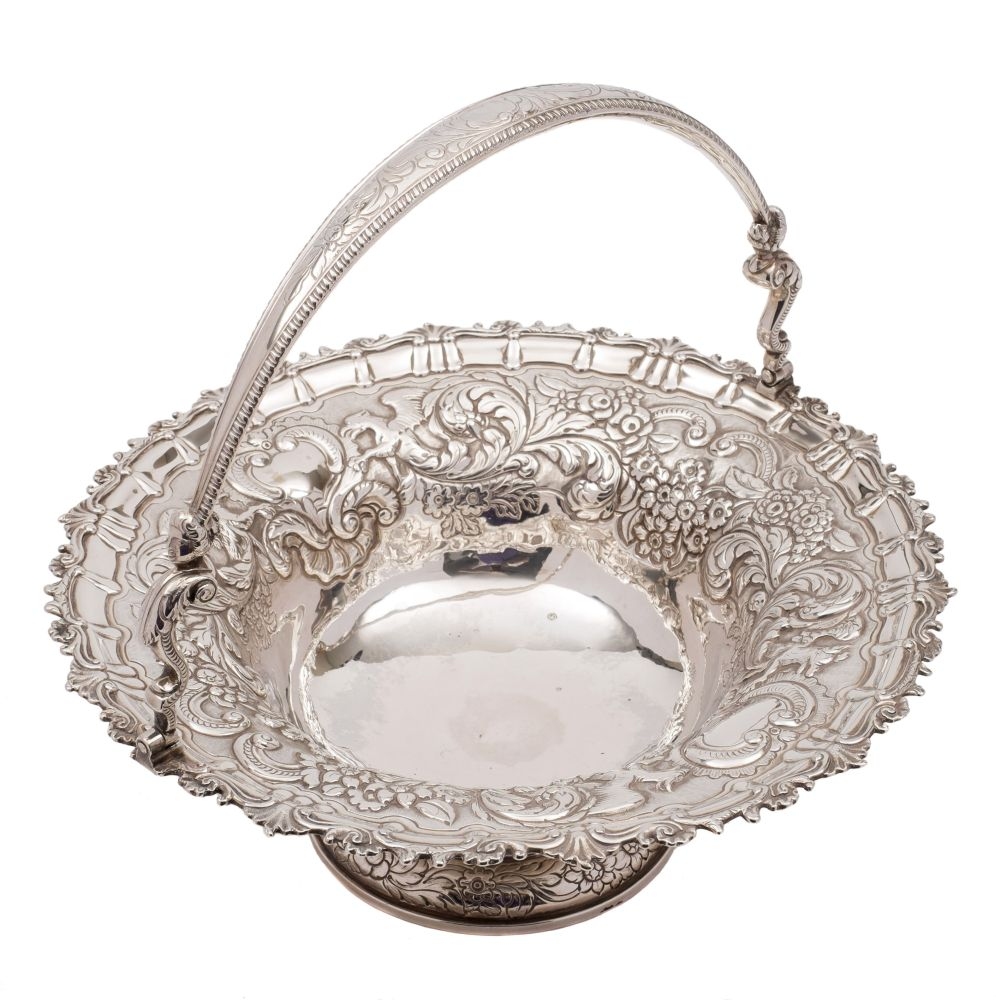 Sale FS38; Lot: 0185: A George III/George IV Irish silver swing handled basket, maker Stephen Bergin, Dublin, 1819? inscribed under the foot, of circular outline with embossed decoration of griffins, fruit, scrolls and foliage, with loop handle on caryatid hinges, raised on a spreading circular foot, 34.5cm diameter, 40.38ozs.