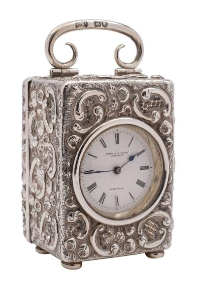 A late Victorian silver boudoir timepiece, maker Mappin & Webb, London, 1899 the 3.5cm Roman dial signed Mappin & Webb, the movement with lever platform escapement contained in an embossed rectangular silver case with loop carrying handle, raised on bun feet, 9cm high.