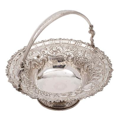 A George III/George IV Irish silver swing handled basket, maker Stephen Bergin, Dublin, 1819? inscribed under the foot, of circular outline with embossed decoration of griffins, fruit, scrolls and foliage, with loop handle on caryatid hinges, raised on a spreading circular foot, 34.5cm diameter, 40.38ozs.