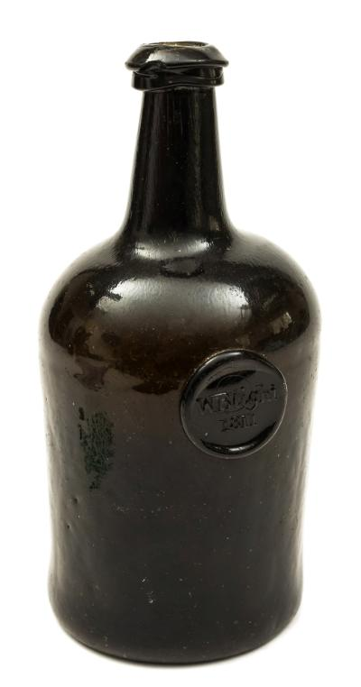 Sale FS39; Lot: 0401: A sealed squat cylinder wine bottle the dark olive/ brown body with pronounced kick up and short tapering neck with an applied triangular string rim, the body applied just below the shoulders with a circular seal for 'W. Blight 1811', 23cm high, small rim chip.