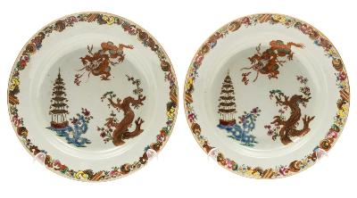Sale FS39; Lot: 0415: A pair of Chinese famille rose plates each painted with a dragon chasing a flaming pearl, a knarled prunus tree, a seven-tiered pagoda and pierced rockwork, Qianlong, 22 cm.