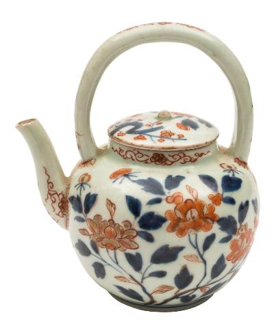 Sale FS39; Lot: 0480: A Japanese Imari teapot and cover with arched overhead handle, painted in underglaze blue and iron-red with branches of peony and prunus, early 18th century, 14cm high.