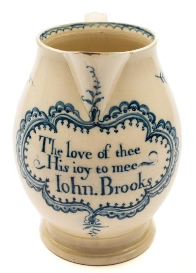 Sale FS39; Lot: 0497: A late 18th century blue and white creamware jug with ogee strap handle, painted with floral sprays and a moth, the front inscribed 'The love of thee/His joy to mee/John.Brooks' in an elaborate foliate cartouche, circa 1780-90, 19.5 cm.