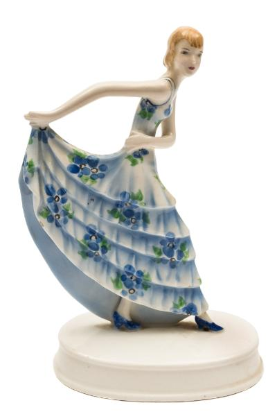Sale FS39; Lot: 0513: A Goldscheider figure of a dancer modelled after the original by Stephan Dakon lifting her blue floral dress behind her, on an oval base impressed Dakon, impressed Goldscheider Wein, Made in Austria with facsimile signature and 8010 and 765, circa 1935, 17cm high.