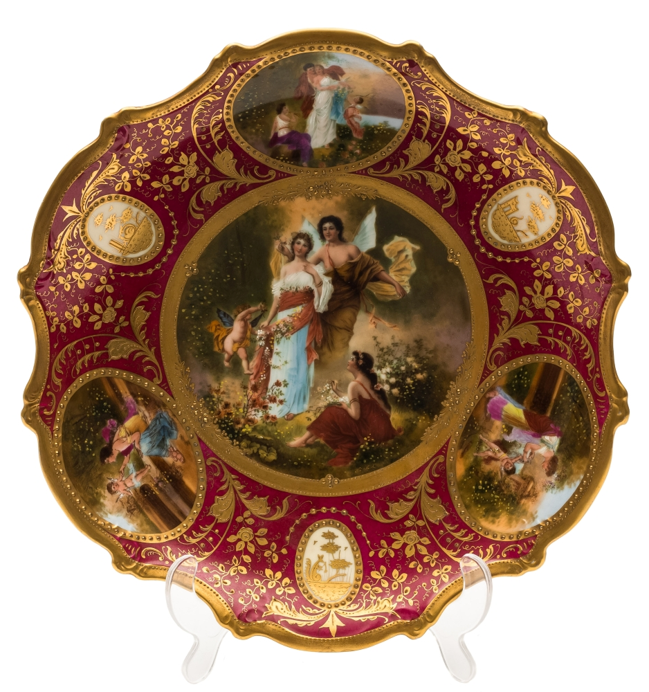Sale FS39; Lot: 0564: A 'Vienna' porcelain plate of silver shape the centre decorated with Cupid Psyche and others with three similarly decorated subsidiary panels reserved on a richly gilt burgundy border containing three medallions, the centre indistinctly signed, bears over glaze gold shield mark to reverse, 19th century, 30cm diameter.